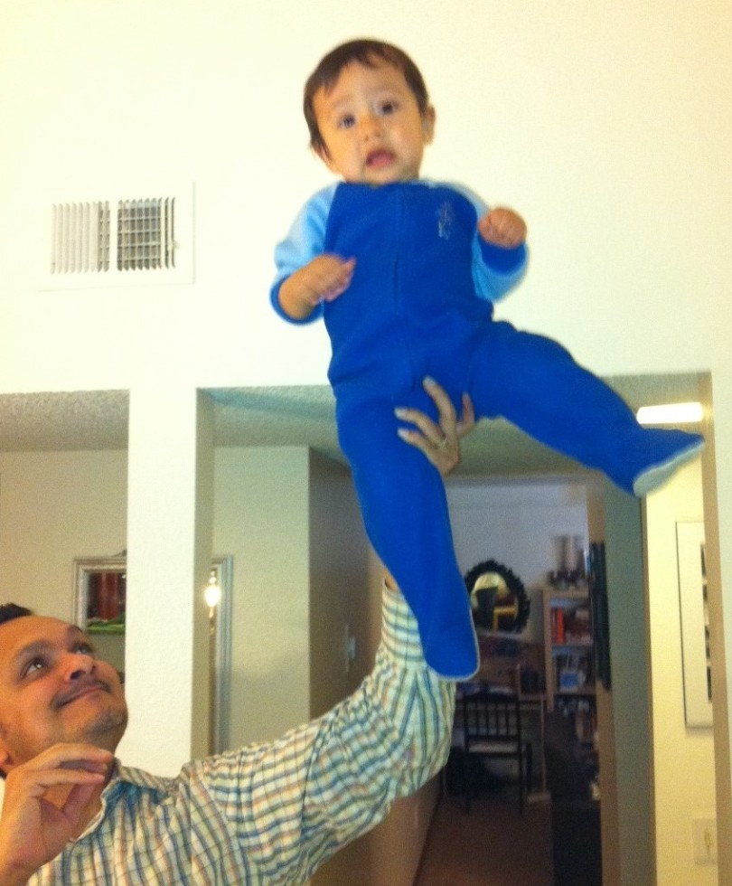 daddy holds baby high