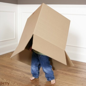 little boy playing with carboard box