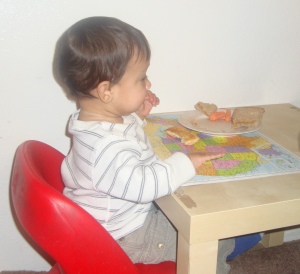 infant sitting on chair eating