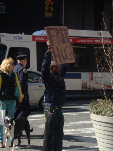 "guy holding ""free hugs"" sign"
