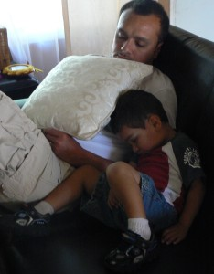 father and son fall asleep on couch