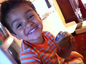 little boy smiling with cupcake on hand