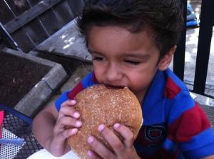 little boy eating hamburger